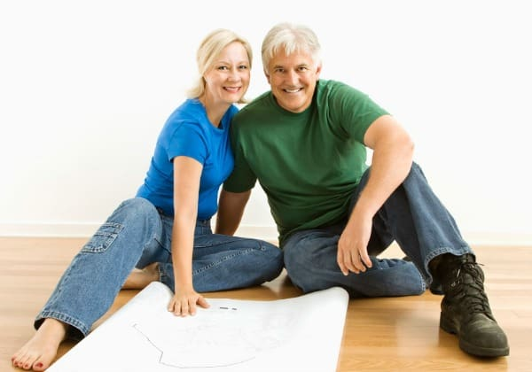 Middle-aged couple sitting on floor with architectural blueprints.