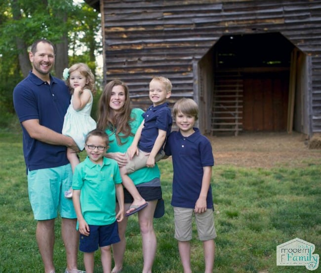 family-smiling-in-front-of-barn-